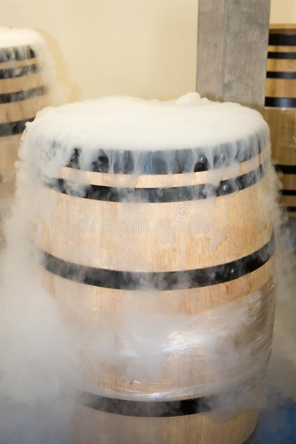 Cellar white smoke dry ice in harvest wooden barrel for refresh grapes during fermentation royalty free stock image