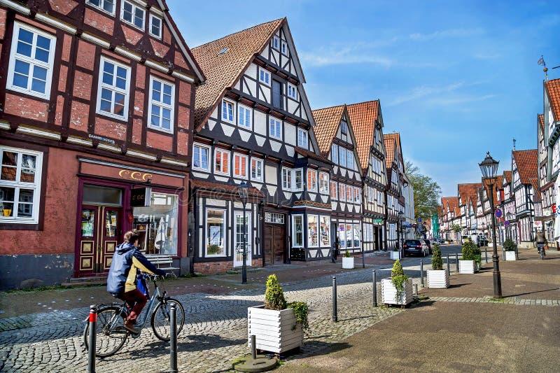 Celle, Alemania - 1 de mayo de 2017: Calle con la fachada del edificio y del hombre que montan una bicicleta en el Celle Ciudad v imagen de archivo libre de regalías