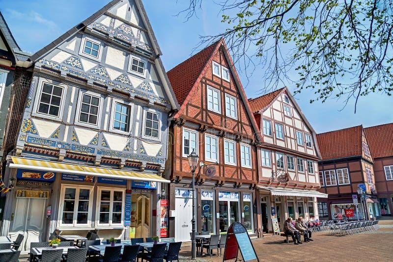 Celle, Duitsland - Mei 1, 2017: Mensen die op de straat met voorgevel van het gebouw in Celle rusten Oude stad in Duitsland stock foto