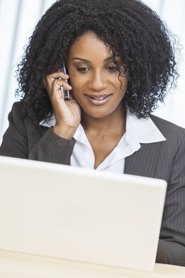 Cellen för afrikansk amerikankvinnaaffärskvinnan ringer bärbar dator royaltyfri fotografi