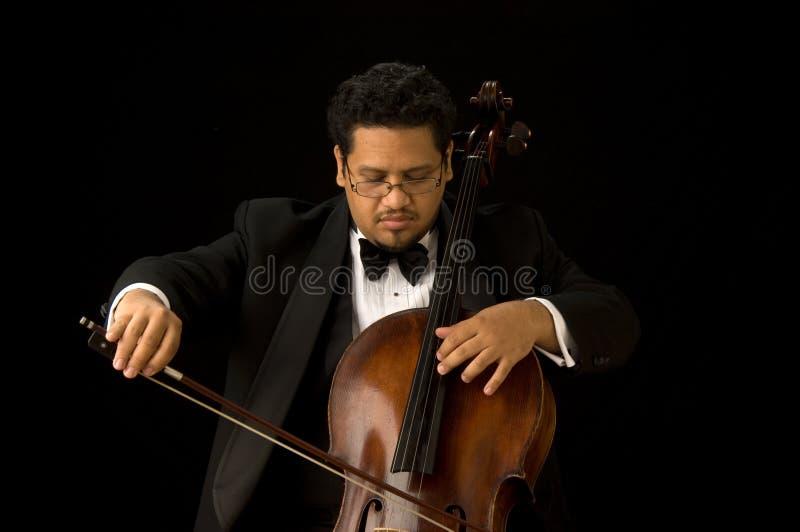 The Cellist. A cello player in a tux with his cello royalty free stock photos