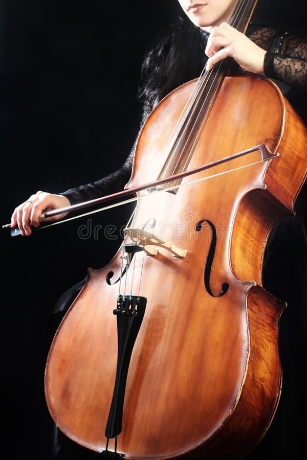 Cellist med det klassiska musikinstrumentet i mörker arkivbilder