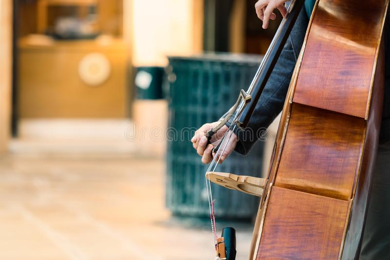Cellist playing with a bow a cello outdoors in Venice, Italy royalty free stock photos