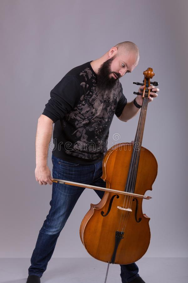 Cellist playing classical music on cello. bearded man fooling around with a musical instrument. Over gray background stock photos