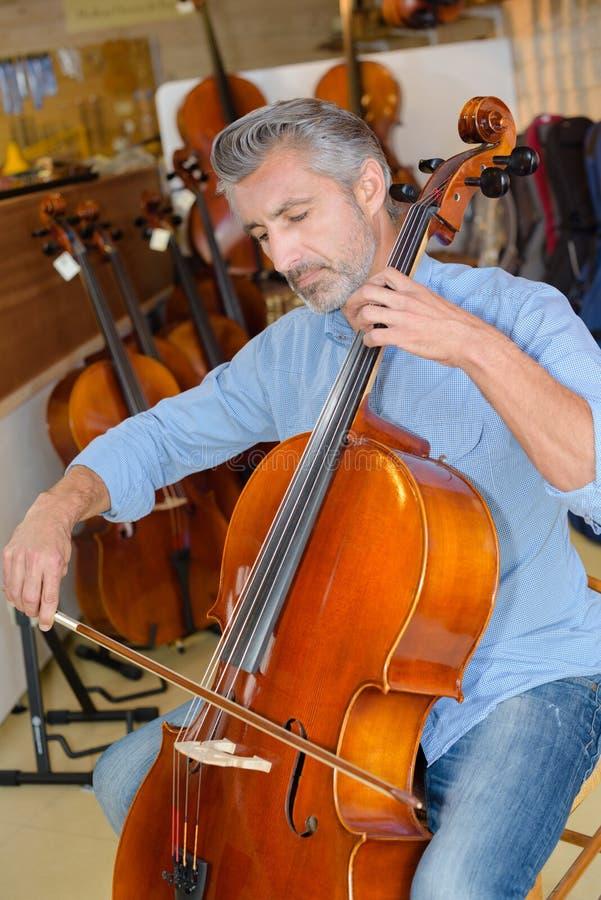 Cellist som testar violoncellen royaltyfri fotografi