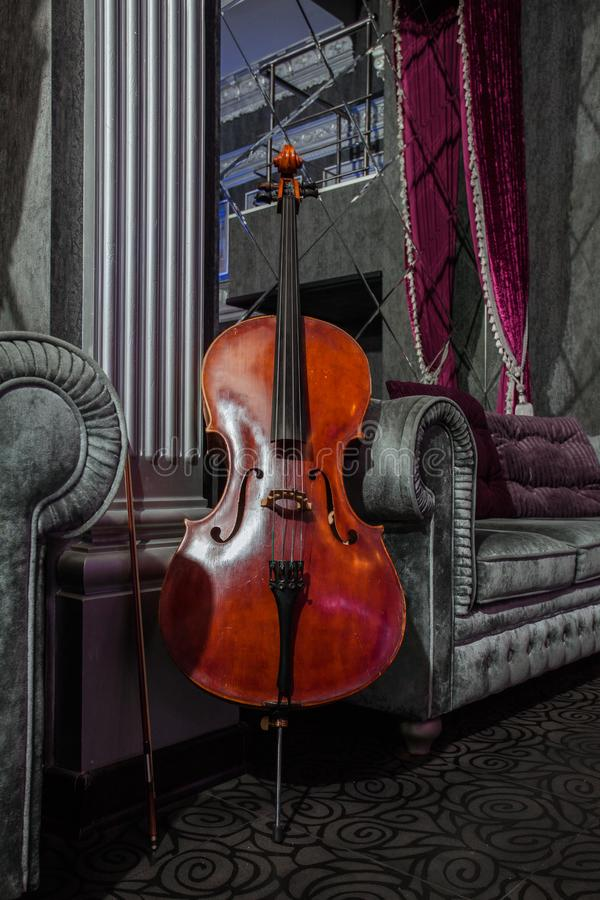 Cello on grey couch. Cello with fiddlestick on the couch in barocue chic interior royalty free stock images