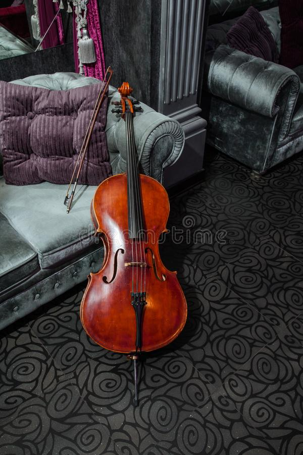 Cello on grey couch. Cello with fiddlestick on the couch in barocue chic interior stock photography