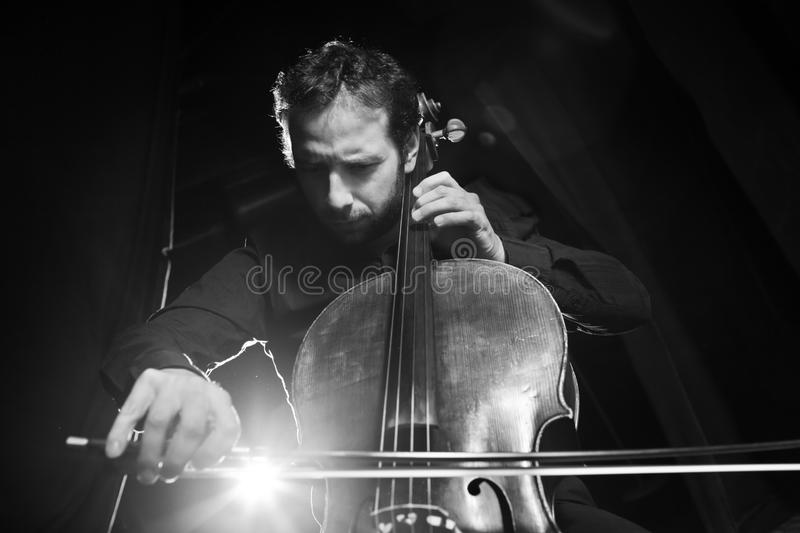 Cello music. Cellist playing classical music on cello on black background