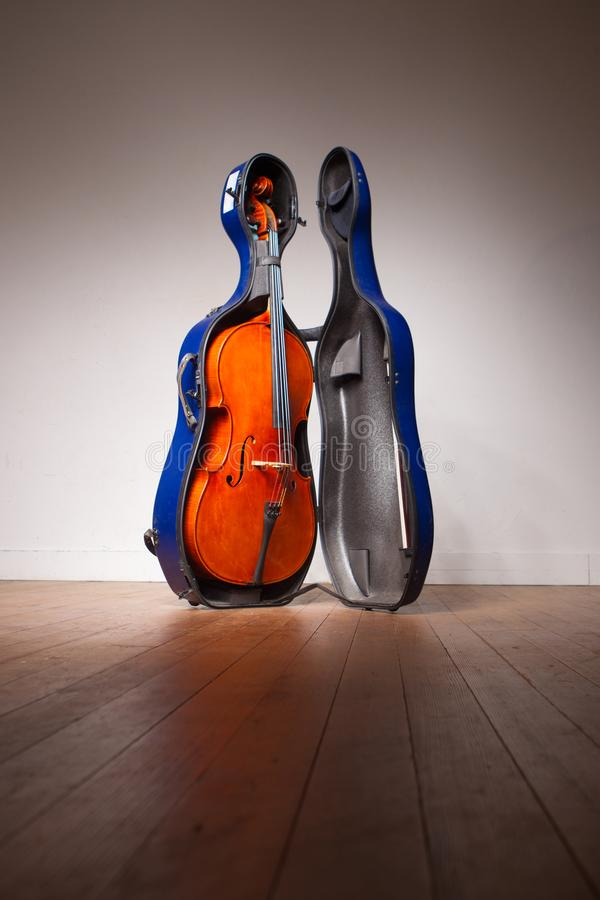 A cello standing in a blue hard case royalty free stock photo