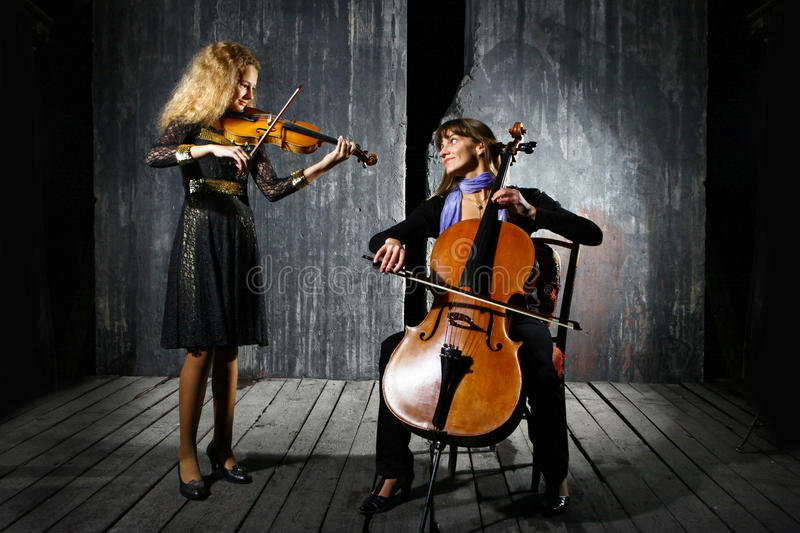 Cello and violin musicians. Daughter and mother playing on cello and violin on grey wall background royalty free stock photography