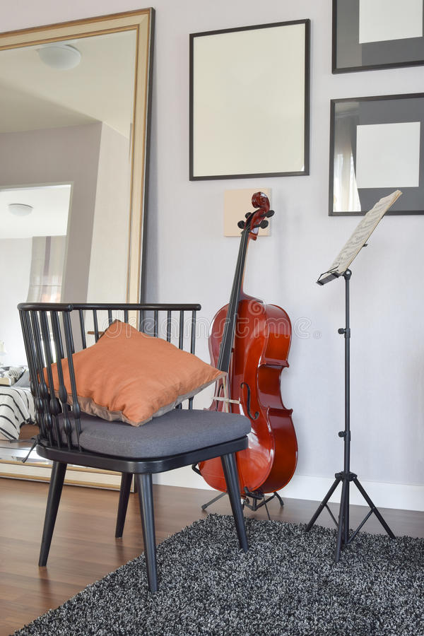 Cello or violoncello musical instrument with wooden chair and pillow. At home stock photo