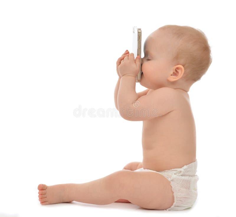 Cellphon mobile baciante sorridente di seduta del bambino del bambino felice del bambino fotografia stock libera da diritti