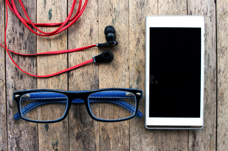 Cellphone and glasses and earphone on wooden background royalty free stock image