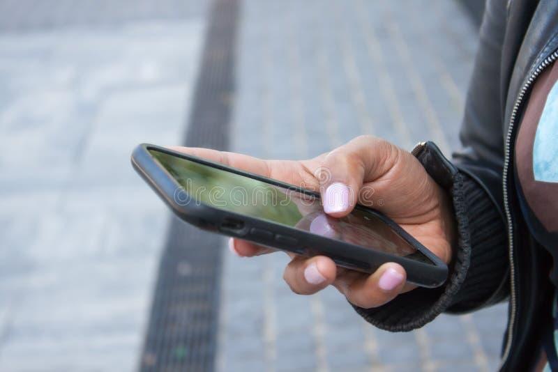 Cellphone in hand. Girl holding black cellphone in her hand on street stock image