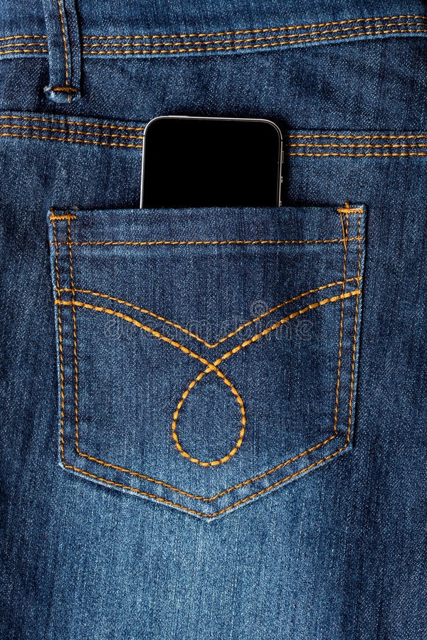 Cellphone in jeans pocket. Mobile phone in denim jeans back pocket royalty free stock image