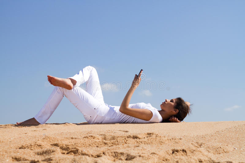 Cellphone sms. Young woman relaxing and lying on beach reading sms from a cellphone royalty free stock photo