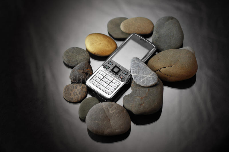 Cellphone and stones stock photography
