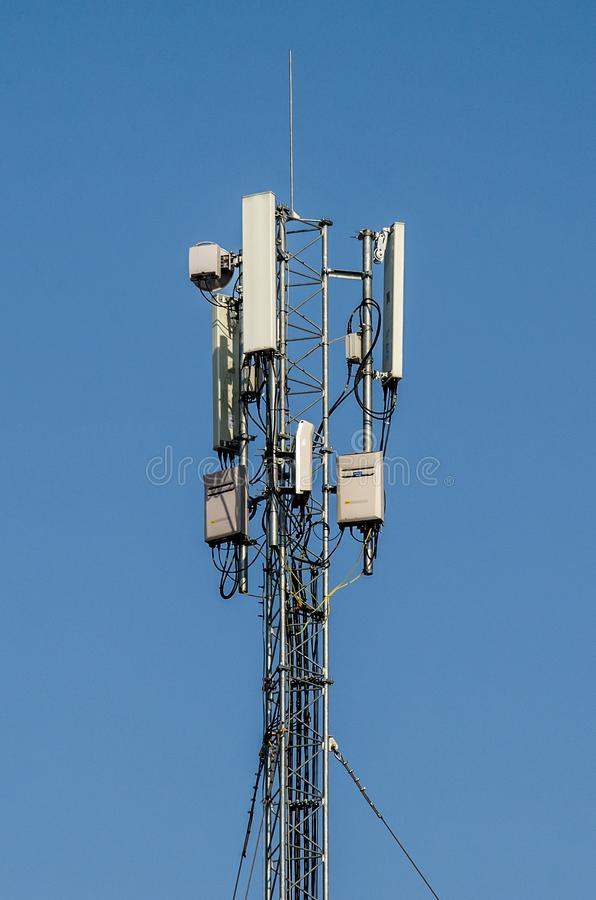 Cellphone tower on a blue background. Radio antenna Tower. royalty free stock photo