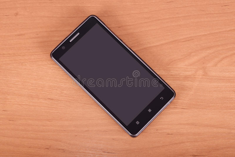 Cellphone on wooden background royalty free stock photography