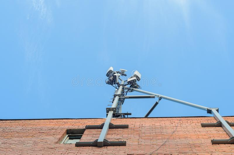 Cellular antenna on the roof of a brick house on blue sky background. stock photo