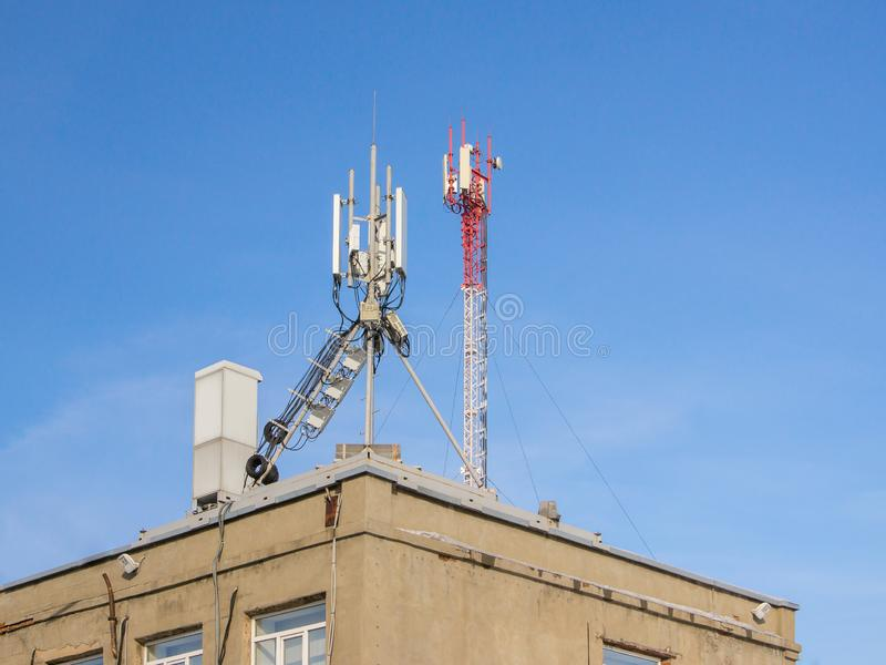 The cellular communication aerial on a building roof. Cell phone telecommunication tower. Antennas on top of building. Telecommunication base stations network stock photography