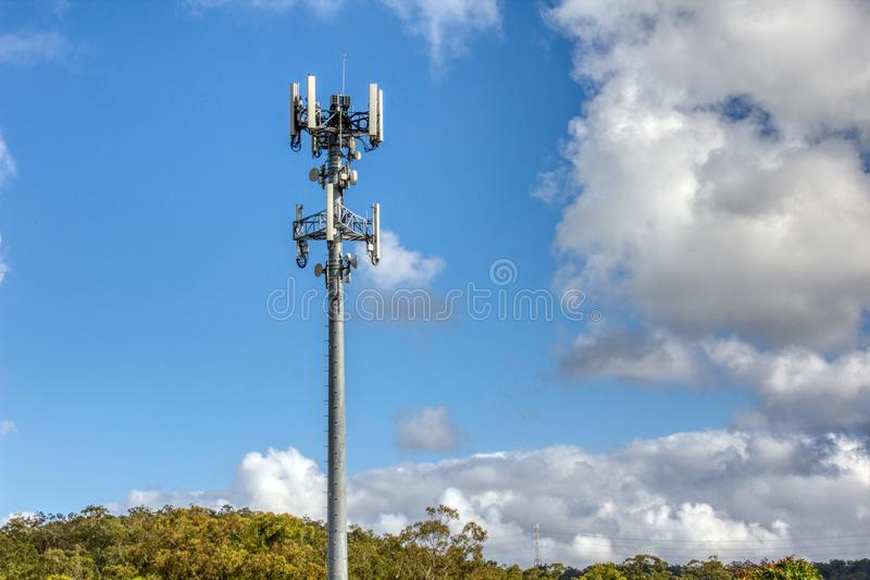 Cellular, mobile phone transmitter tower with blue sky and clouds left stock photo