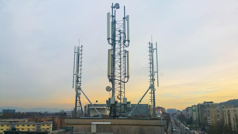 Cellular network antenna radiating and broadcasting strong power signal waves. Over the city on a building roof with telecommunication mast stock photo