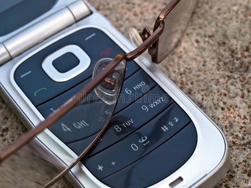 Cellular phone and eye glasses stock photos