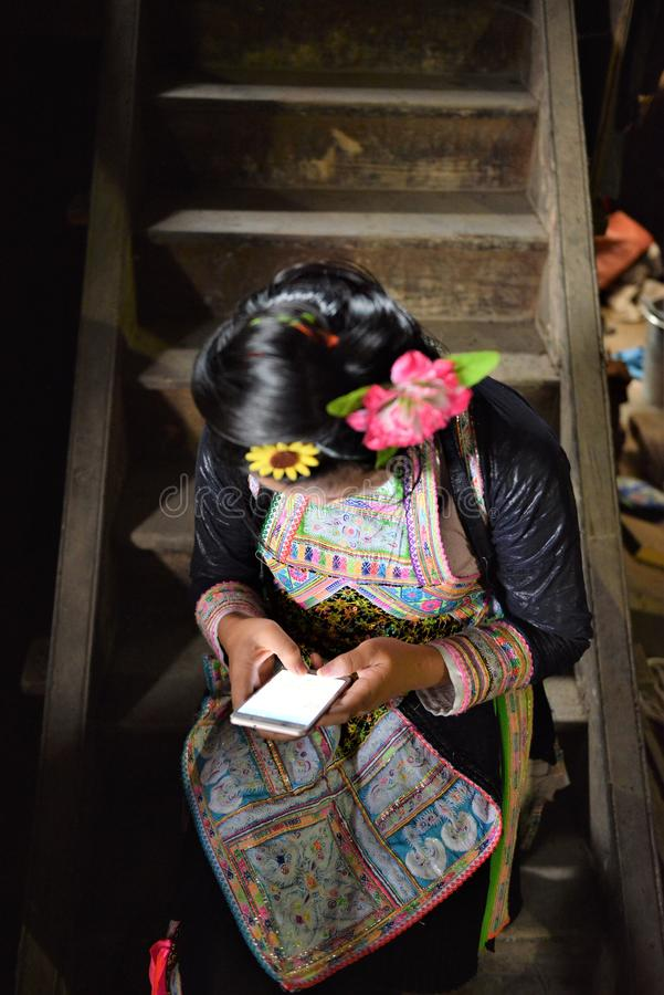 Cellular phone is global reached to the miao tribes in china. Mia tribe girl dressed in traditional costumes chats on the cellular phone in china royalty free stock photography