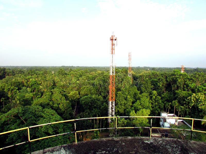 Cellular tower into the green forest view from water tank royalty free stock photo