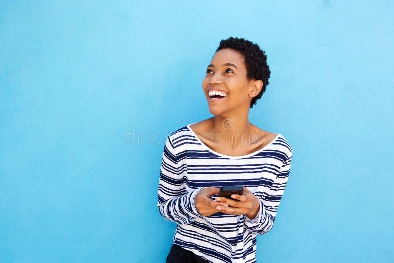 Cellulare afroamericano attraente della tenuta della donna dalla parete blu immagini stock
