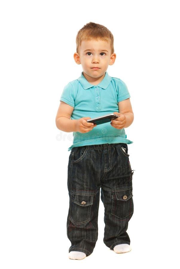 Cellulare di pensiero della holding del bambino fotografia stock