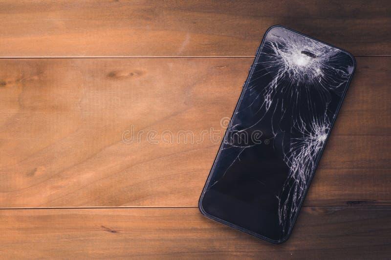 Cellulare di Smartphone con uno schermo rotto legno del fondo fotografia stock libera da diritti