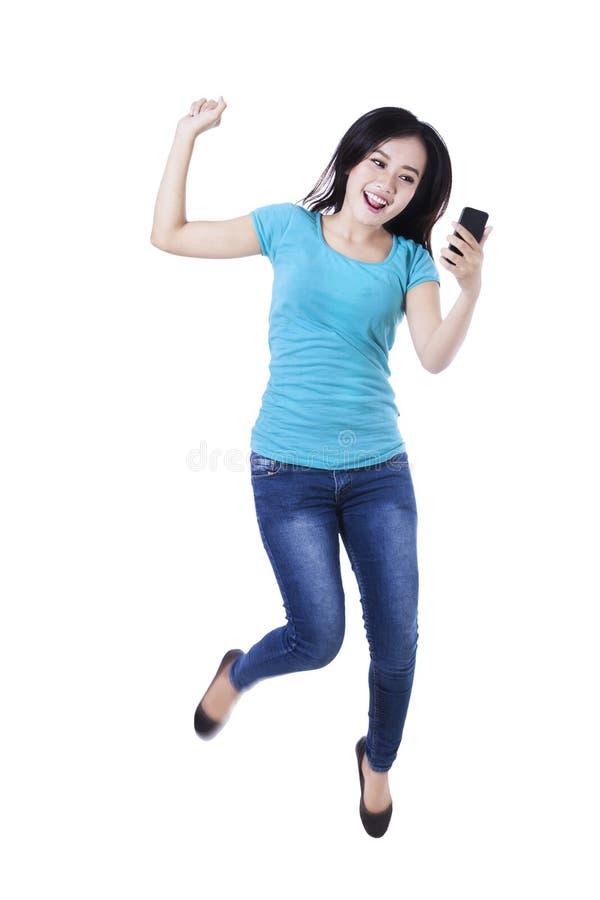 Cellulare e salto della tenuta della donna fotografia stock libera da diritti