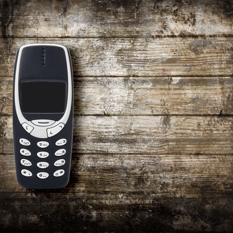 Cellulare obsoleto su fondo di legno fotografie stock