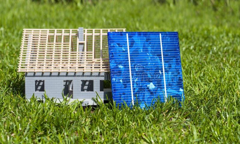 Cellules ? ?nergie solaire avec le globe de glas et la maison miniature dans l'herbe verte photos libres de droits