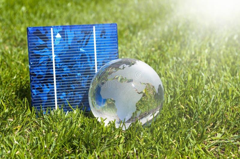 Cellules ? ?nergie solaire avec le globe de glas et la maison miniature dans l'herbe verte photographie stock libre de droits