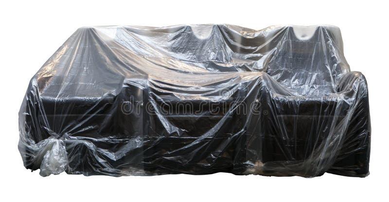 Celofane do sofá coberto colhido no branco imagens de stock royalty free