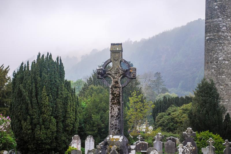 Celtic cross in a cementery at Glendalough Ireland. Celtic cross in the middle of a cementery, and a forrest and a cloudy blue sky stock images