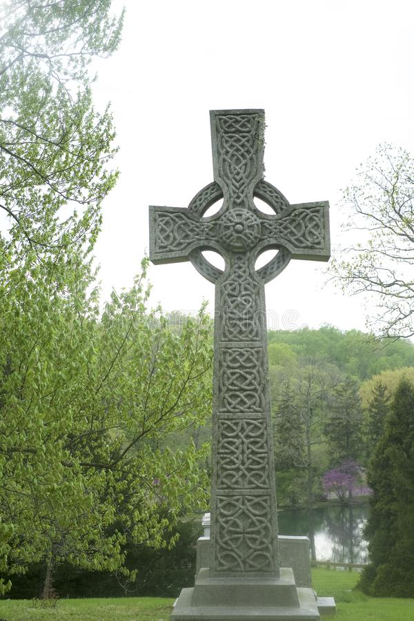Celtic cross Tombstone in graveyard  woman in mourning royalty free stock image