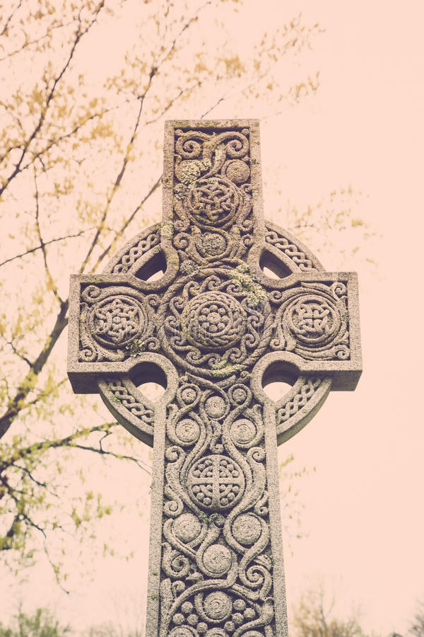 Celtic Cross Tombstone. A Celtic cross tombstone with ornate details in an old cemetery stock photo