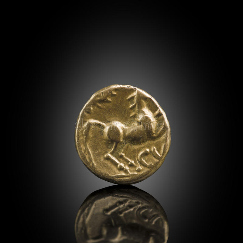 Celtic gold stater. Old Celtic coin showing horse, exposed on bl. Ack reflecting glass, found in life dig by metal detector.England stock photography