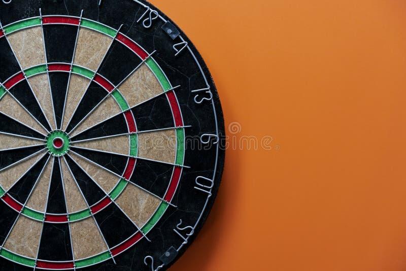 Celuje strzałki deskę na stole z pomarańczowym tłem, centrum punktem, głową celu marketing i biznesowego sukcesu pojęciem, obrazy royalty free