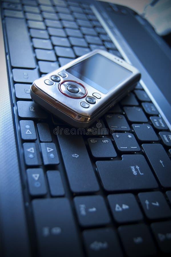 Celular en una computadora portátil imágenes de archivo libres de regalías