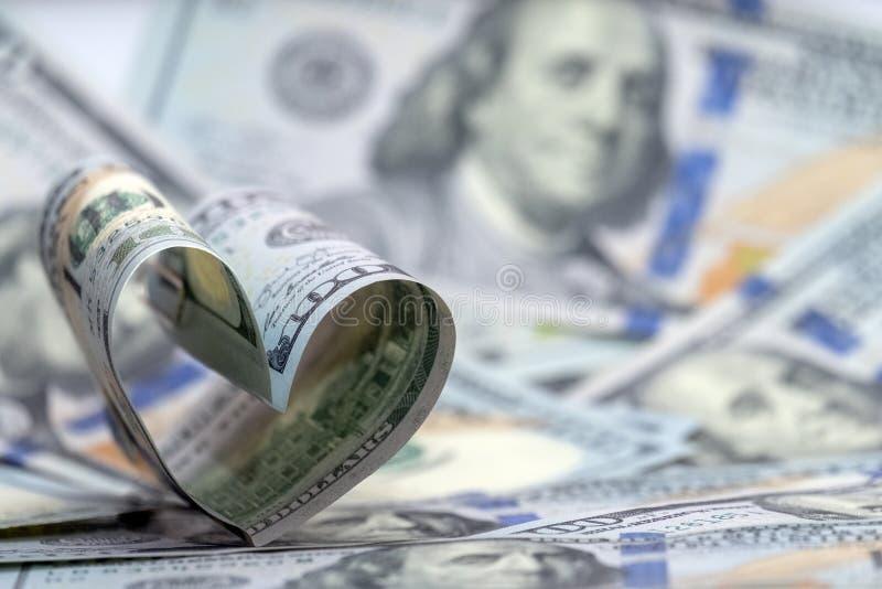 Cem cédulas do dólar dos EUA na forma de um coração Fundo do dinheiro Amor financeiro do conceito e um presente para o dia de Val fotos de stock