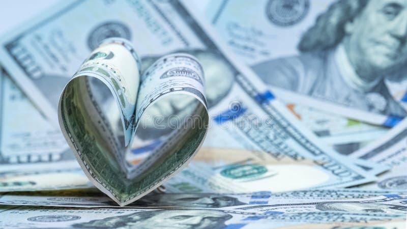 Cem dólares de cédula dos E.U. na forma de um coração Fundo do dinheiro Amor financeiro do conceito e um presente para o dia de V fotografia de stock royalty free