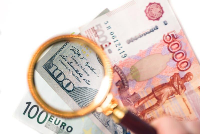 Cem dólares sob uma lupa nas cédulas do euro e do rublo do bacdrop fotografia de stock royalty free