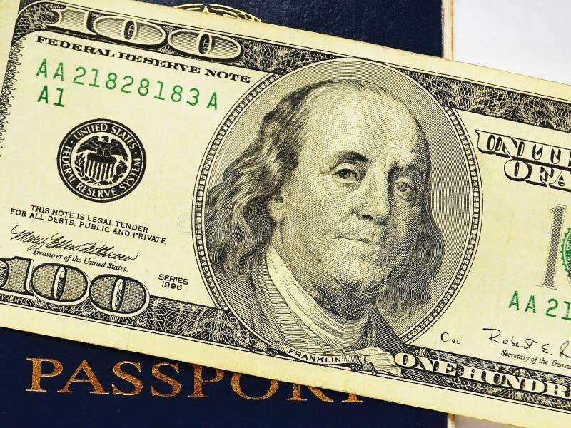 Cem notas de dólar em um fim azul do passaporte acima fotos de stock