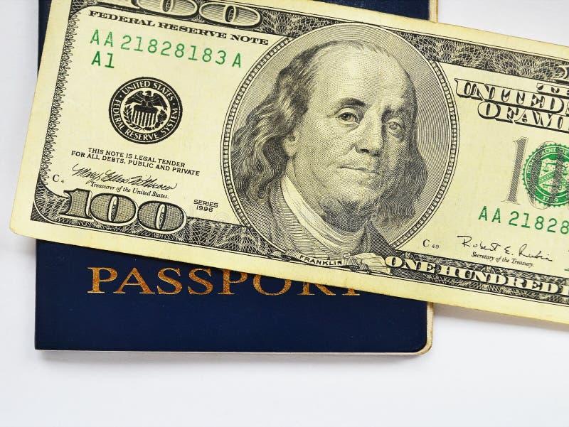 Cem notas de dólar em um fim azul do passaporte acima fotografia de stock royalty free
