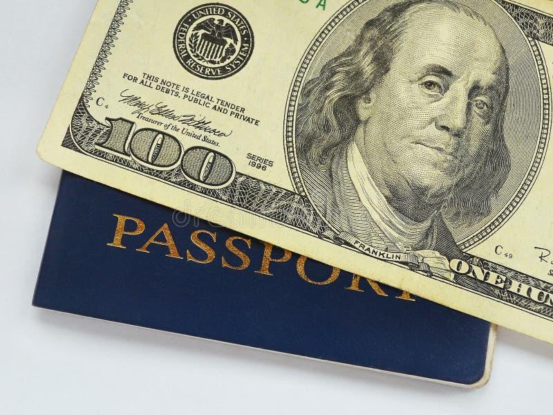 Cem notas de dólar em um fim azul do passaporte acima foto de stock